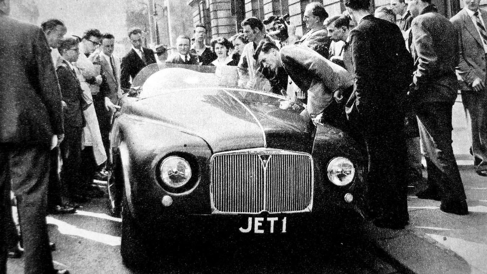 Лавры создания первого в мире газотурбинного легкового автомобиля принадлежали британской компании Rover, инженеры которой впервые познакомилась с такими агрегатами во время Второй мировой войны при секретных разработках авиационных и танковых газовых турбин.Первый в мире газотурбинный автомобиль Rover Jet-1 удивлял всех прохожих в Лондоне. 1950 годВ 1946 году, не имея понятия, к чему приведут её старания, фирма Rover приступила к созданию экспериментальной открытой двухместной машины Jet-1 с задним расположением двигателя. Затем ушло еще три года на доработку базового легкового шасси Р-4 без коробки передач, на выбор схемы ГТД и испытания первого работоспособного двигателя Т-5 в 100 сил. Его центробежный компрессор вращался с частотой до 40 тысяч оборотов в минуту, а вал турбины развивал 26 тысяч, для чего была введена понижающая передача на колеса.Опробование второго более мощного турбоавтомобиля Rover Jet-1. 1952 год (фото R. Gerelli)Публичная демонстрация автомобиля Jet-1 сопровождалась шумной рекламной кампанией (фото R. Gerelli)Презентация Jet-1 состоялась в марте 1950 года. Через два года начались испытания модернизированного варианта с 230-сильной турбиной Т-8. Такой ГТД отличался плавностью работы, но слишком высокая рабочая температура потребовала применения редких и дорогих материалов, а расход авиационного керосина достигал 50 литров на 100 километров.Единственная сохранившаяся машина Rover Jet-1 образца 1950 года в лондонском Музее науки (фото автора)В 1956 году фирма Rover вернулась к ГТД второго поколения с новой 100-сильной турбиной 2S/100 и теплообменником производства компании British Leyland. Ее смонтировали в задней части полноприводного автомобиля Т-3 с двухместным стеклопластиковым кузовом на сварной раме с алюминиевыми усилителями и дисковыми тормозами. Максимальная скорость достигала 170 км/ч, расход топлива сократился до 22 литров, но в то время компания уже не могла выделить крупных средств на продолжение этих работ.Испытания уникального по