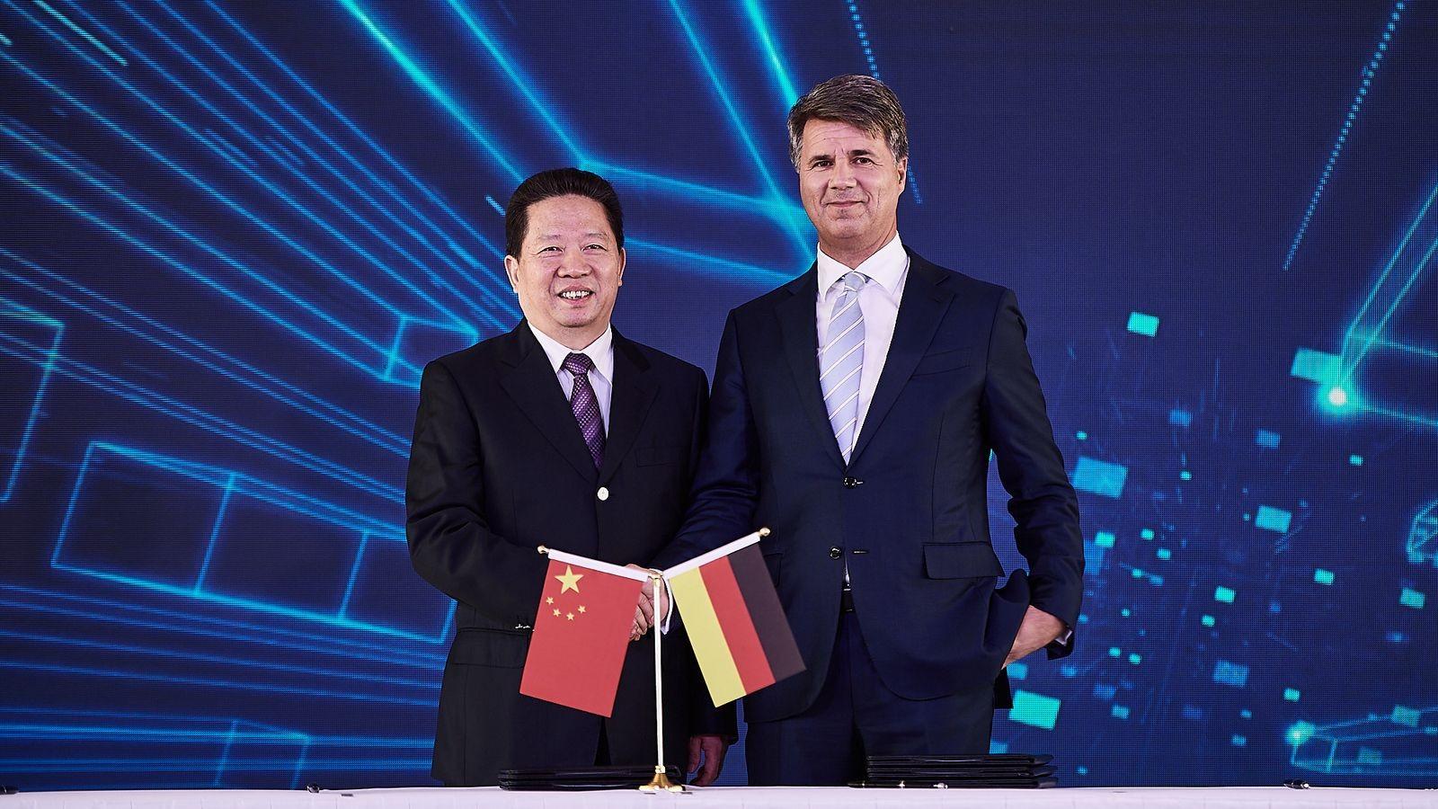 Региональный секретарь Компартии Китая в провинции Ляонин Чен Киуфа и глава BMW Харальд Крюгер жмут руки в знак достижения соглашения о сделке в рамках совместного предприятия BBA.