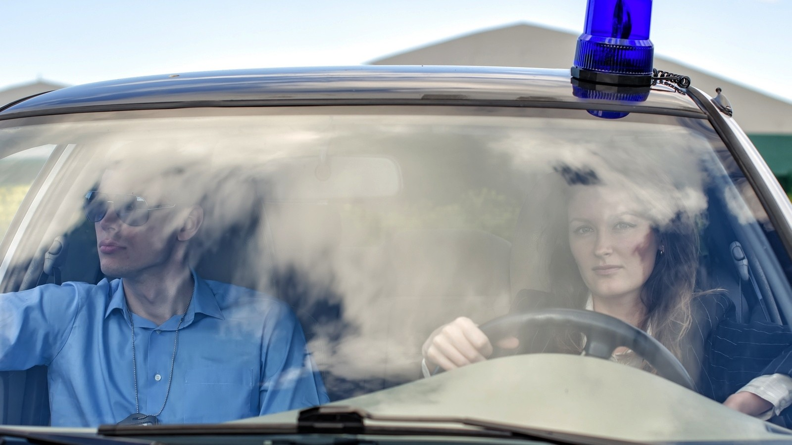 Two young detectives driving to crime scene. Windscreen view