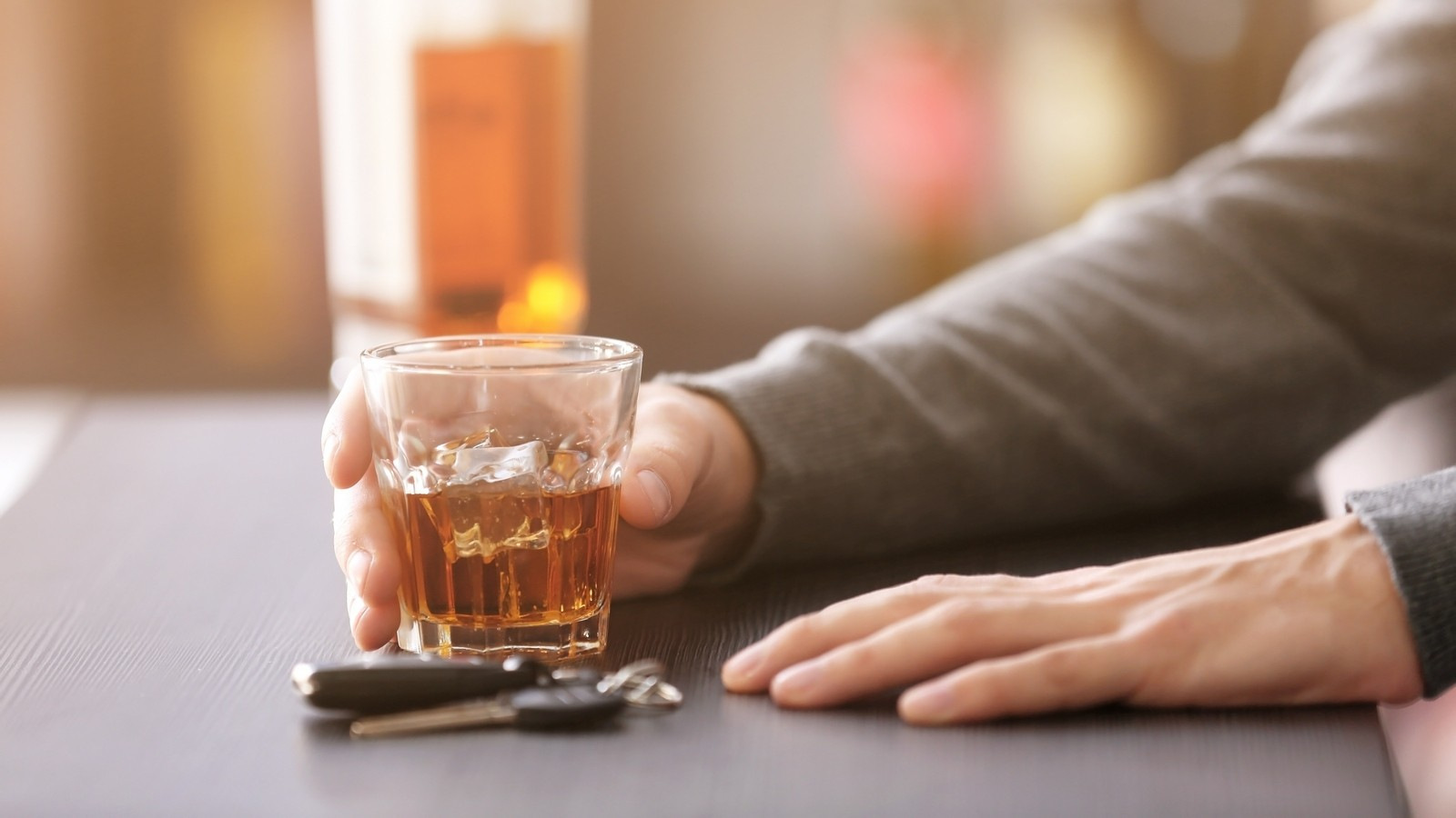Man sitting in bar with car key and glass of alcoholic beverage, closeup. Don't drink and drive concept