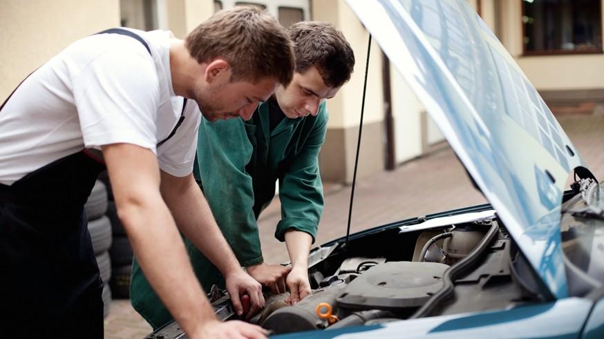 Two auto mechanics working with car