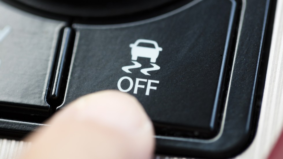 finger pressing Traction Control System button