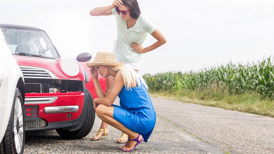 Tensed women looking at damaged cars on road against clear sky