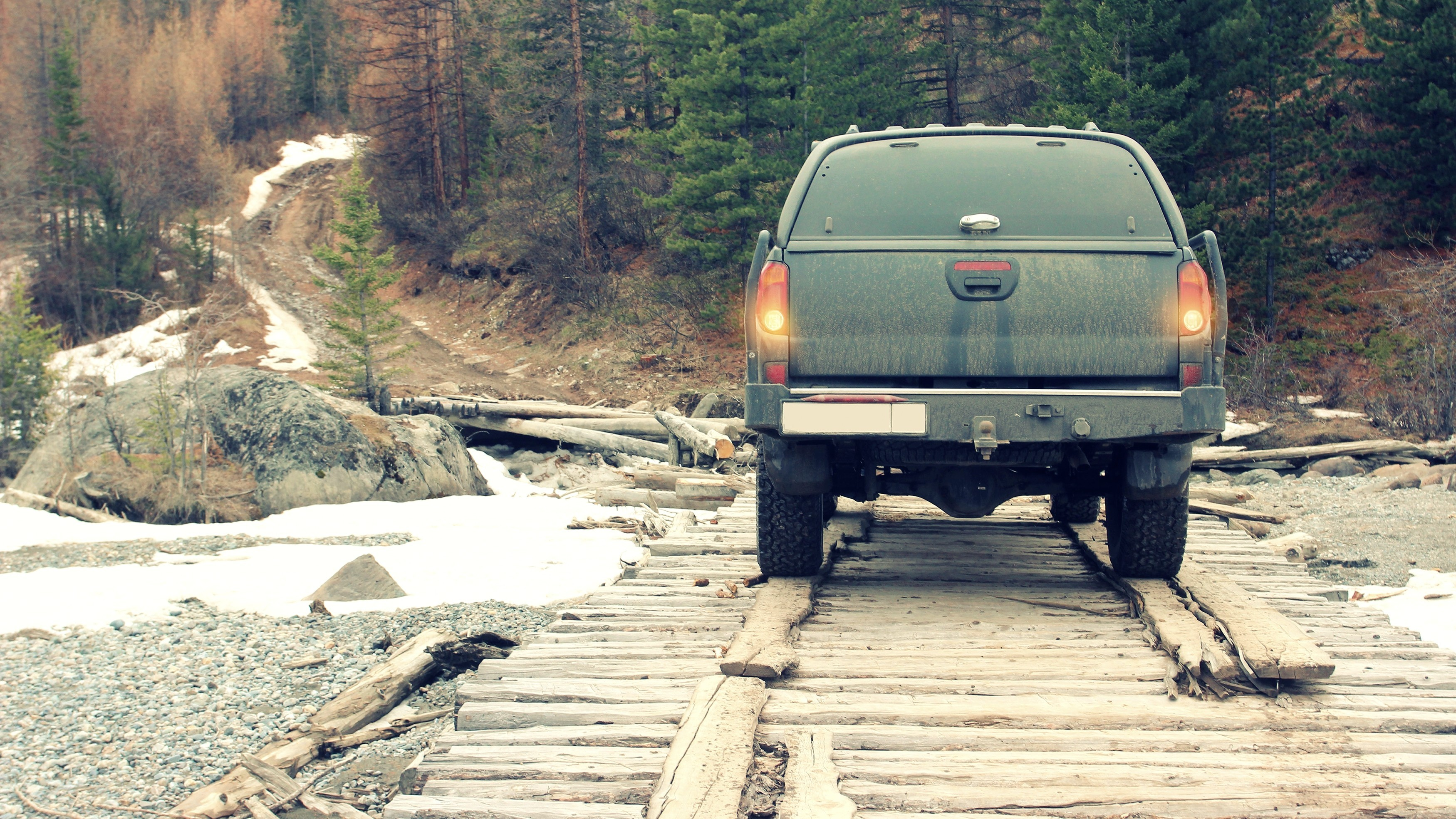 Off-road car on the old bridge into the mountain forest.