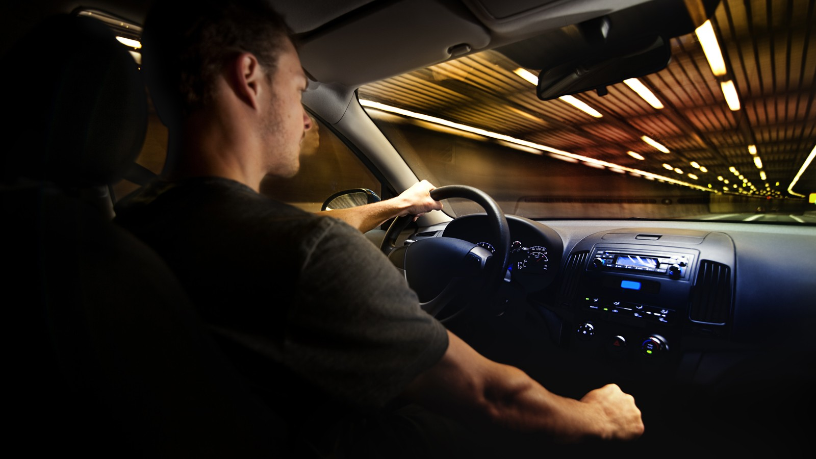 Young Adult Driving Over the Speed Limit in a Tunnel.