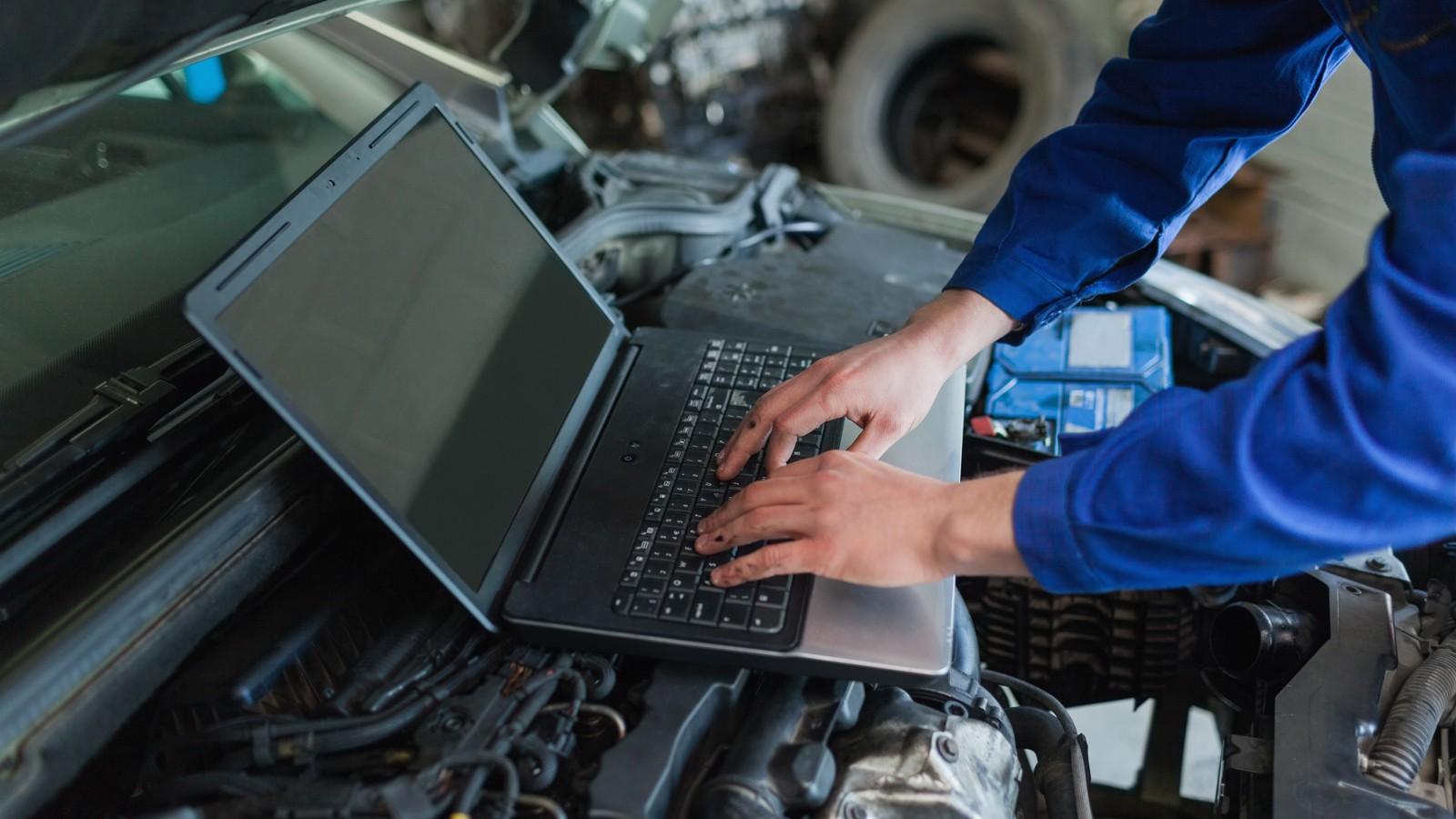 Close-up of auto mechanic using laptop