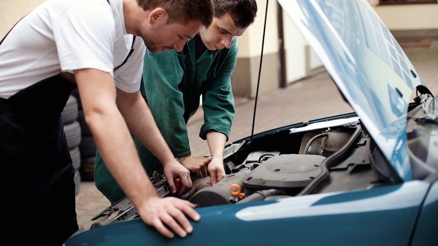 Two auto mechanics working with car