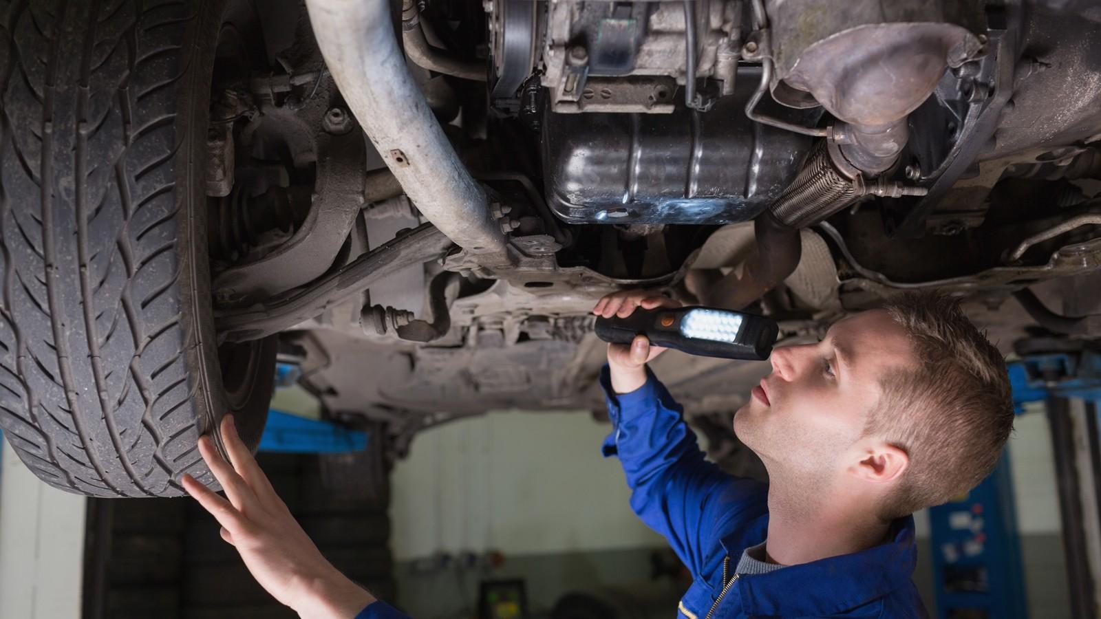 Male mechanic examining car using flashlight