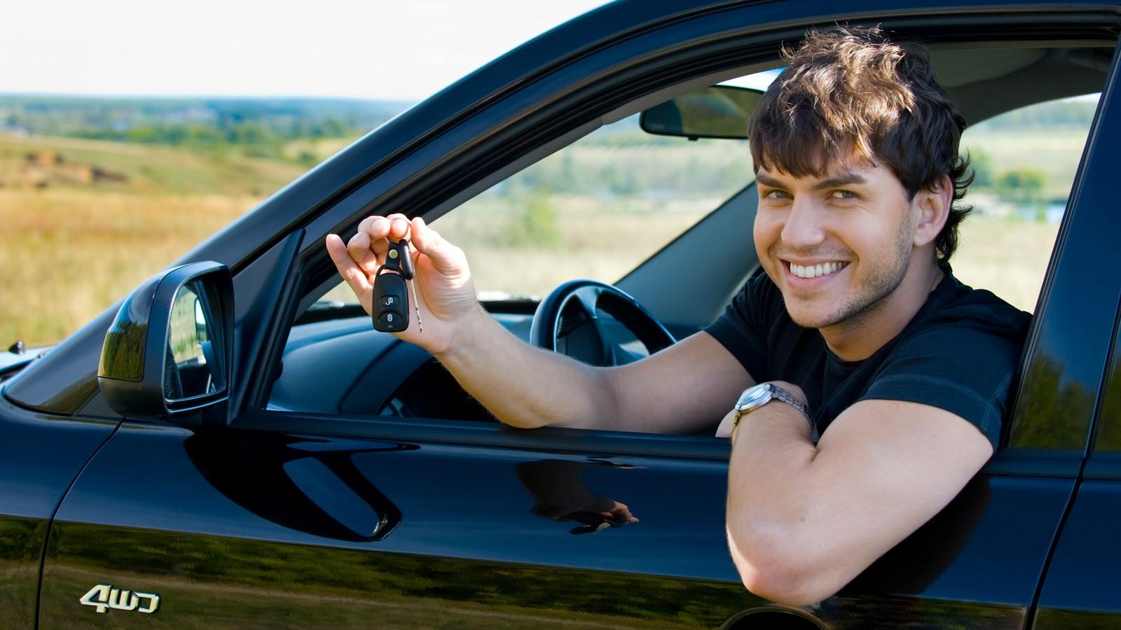 happy man showing keys in car