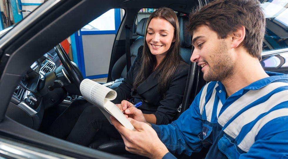 Car mechanic with customer
