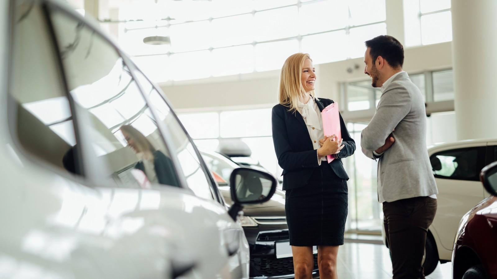Salesperson selling cars at dealership