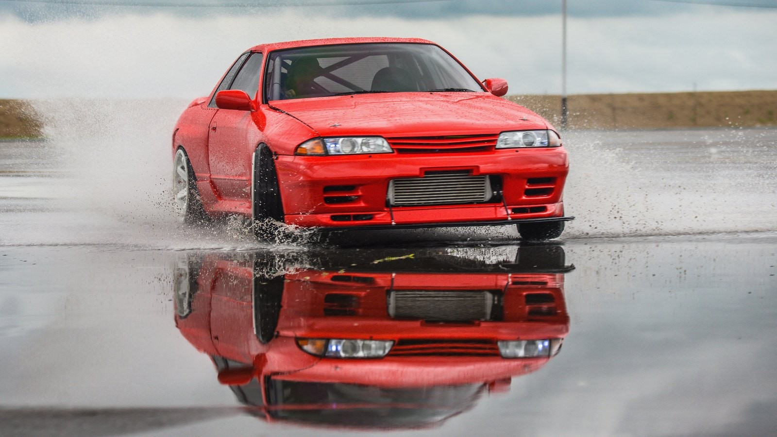 Nissan skyline R 32 red color on a wet road