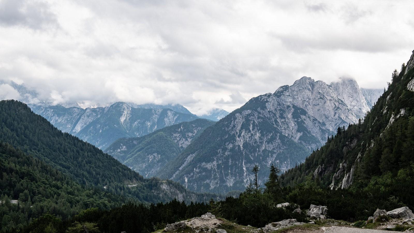 Высшая точка маршрута лежала на высоте 1 611 метров: это перевал Вршич, один из высочайших горных перевалов в этой части Альп. В отсутствие проблем с дыханием или недостатком тяги у машин напоминанием об отметке над уровнем моря были лишь облака, ватными комьями укутывающие вершины гор – до них, казалось, рукой подать. Ну а на самым впечатляющим на спуске было даже не скалистое окружение, а сама дорога, выложенная в поворотах брусчаткой. Это – вечная память о русских военнопленных, которые в годы Первой мировой войны прокладывали путь через перевал. Австро-Венгрия, в состав которой в то время входила территория Словении, стремилась укрепить свои позиции на итальянском фронте, и задействовала для этого пленную рабочую силу. Несколько лавин, сошедших во время строительства и выкосивших русских солдат быстрее голода, болезней и тяжелого труда, погребли под собой сотни человек – и как дань памяти здесь теперь стоит Русская часовня, к которой ведет та самая дорога, выстланная брусчаткой.