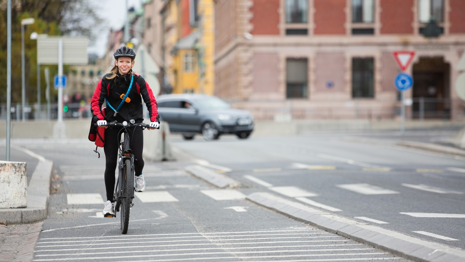 Female Cyclist With Courier Delivery Bag On Street