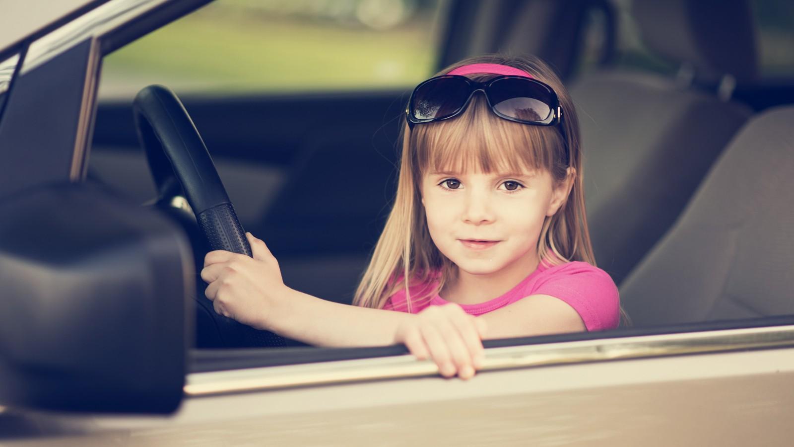 Little girl driving a car.