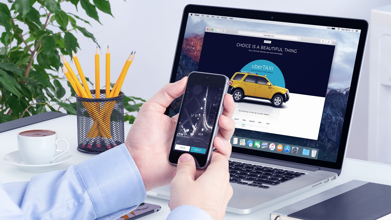 Uber app on the iPhone display in man hands and Uber website on