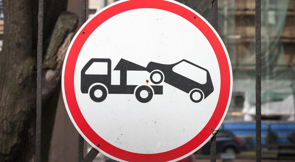 Evacuation on tow truck. Round road sign