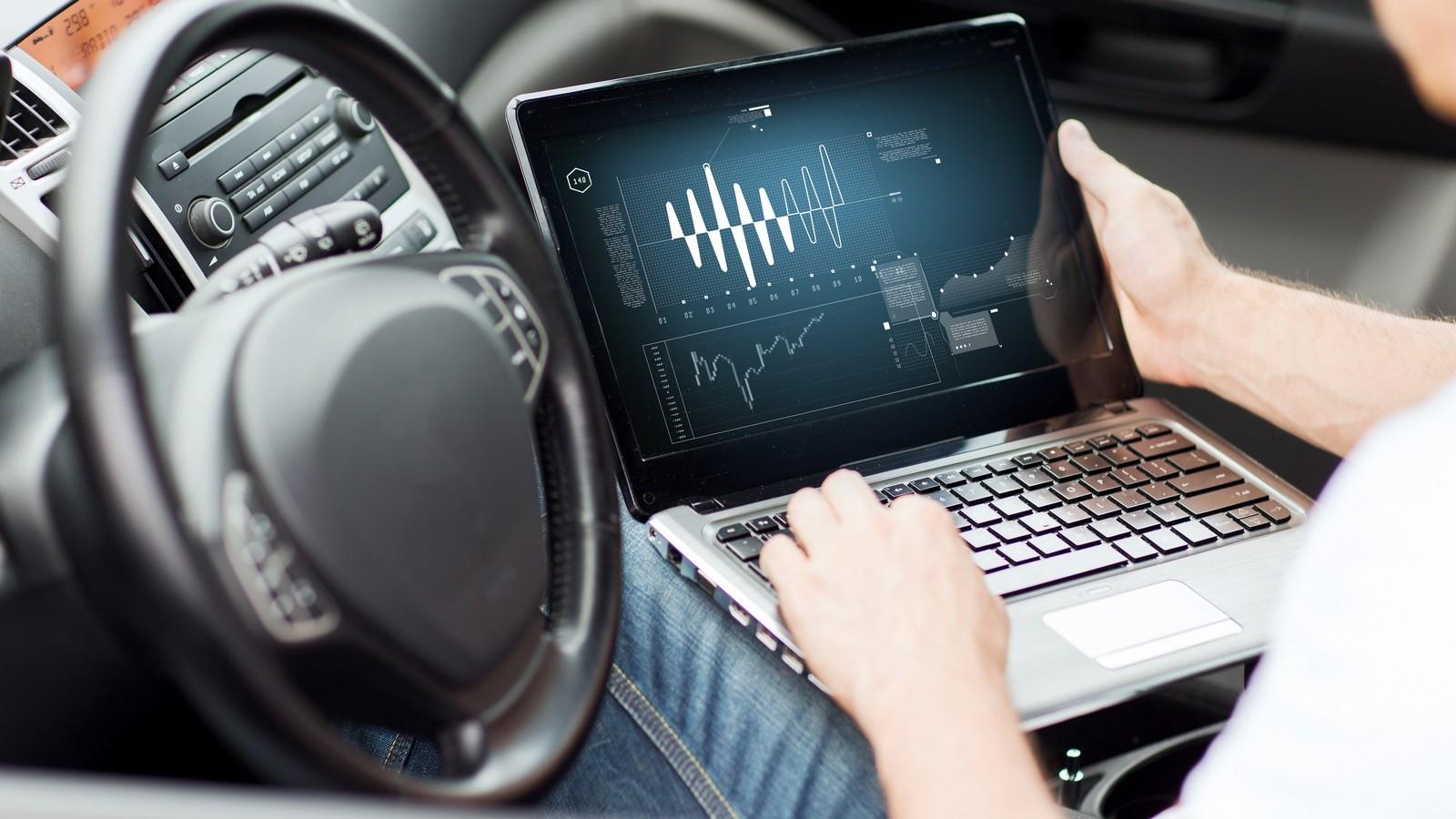 man using laptop computer in car