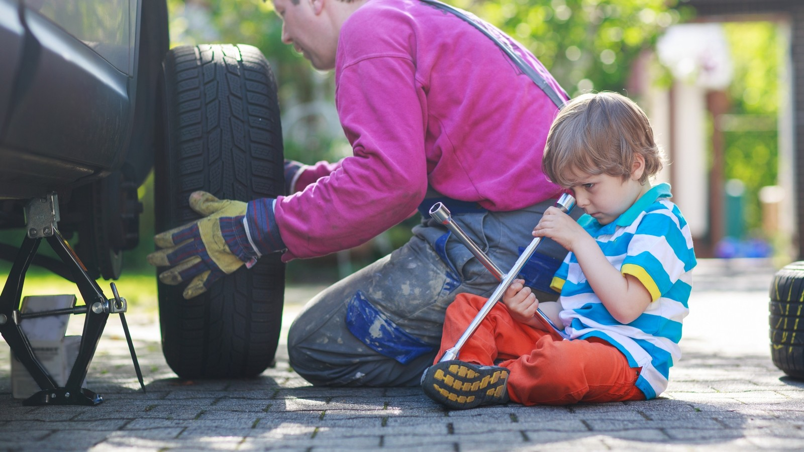 Father and adorable little boy repairing car and changing wheel
