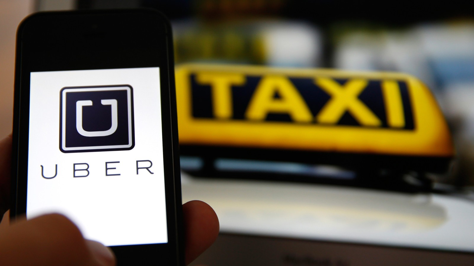 An illustration picture shows the logo of car-sharing service app Uber on a smartphone next to the picture of an official German taxi sign