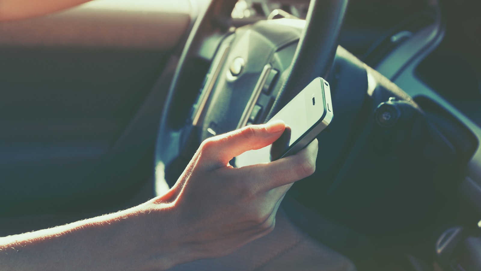 girls hand using smart phone while car driving