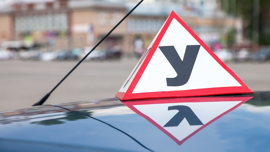 Sign of a Russian Driving School on top of the vehicle